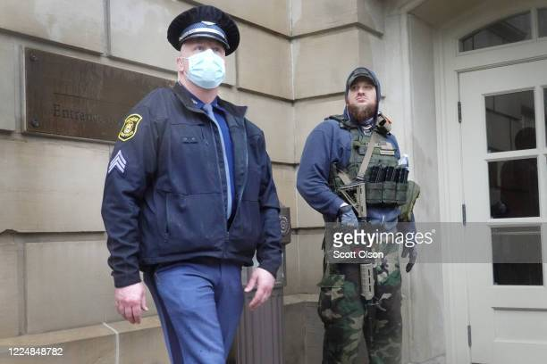 State police officer stands guard during a rally in front of the Michigan state capital building where protesters were demonstrating against the...