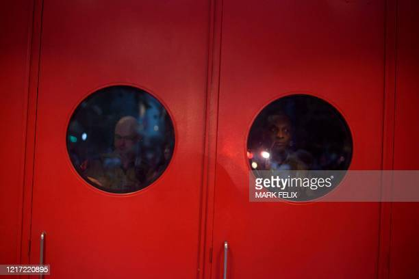 State police officers look through the doors at the Toyota Center during a peaceful march to remember George Floyd in downtown Houston, Texas on...