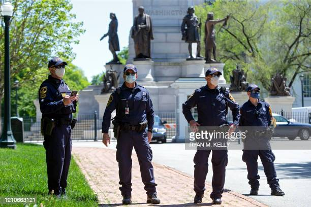 State police officers monitor activity during a reopen Virginia rally around Capitol Square in Richmond on April 22 2020 Protesters were opposed to...
