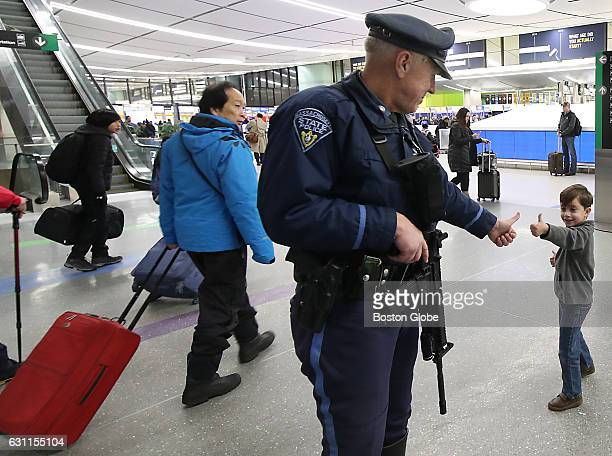 State Police Trooper Albert Manzi Jr gets a thumbs up before a high five from Xavier Melo from Boston at Logan Airport Terminal C Jan 6 2017 Security...
