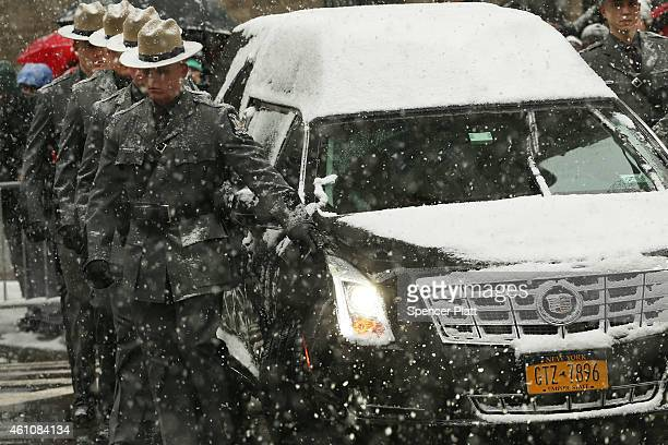 State Police walk with the hearse carrying the casket of former threeterm governor Mario Cuomo into St Ignatius Loyola Church on January 6 2015 in...