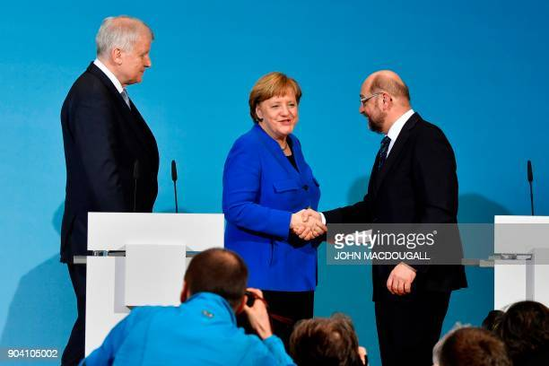 State Premier for the state of Bavaria and leader of the Christian Social Union Horst Seehofer looks on as German Chancellor Angela Merkel shakes...