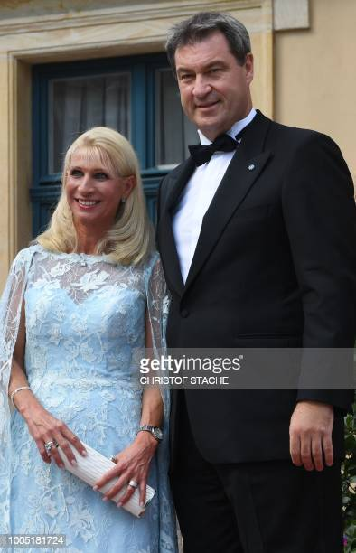 State Premier Markus Soeder and his wife Karin Baumueller poses as they arrive for the opening of the annual Bayreuth Festival featuring the music of...