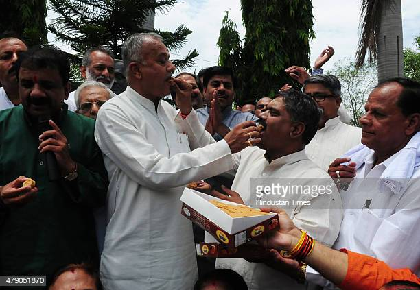 BJP state President Nand Kumar Singh Chauhan sharing sweets with other party leaders to celebrate victory in Garoth by election on June 30 2015 in...