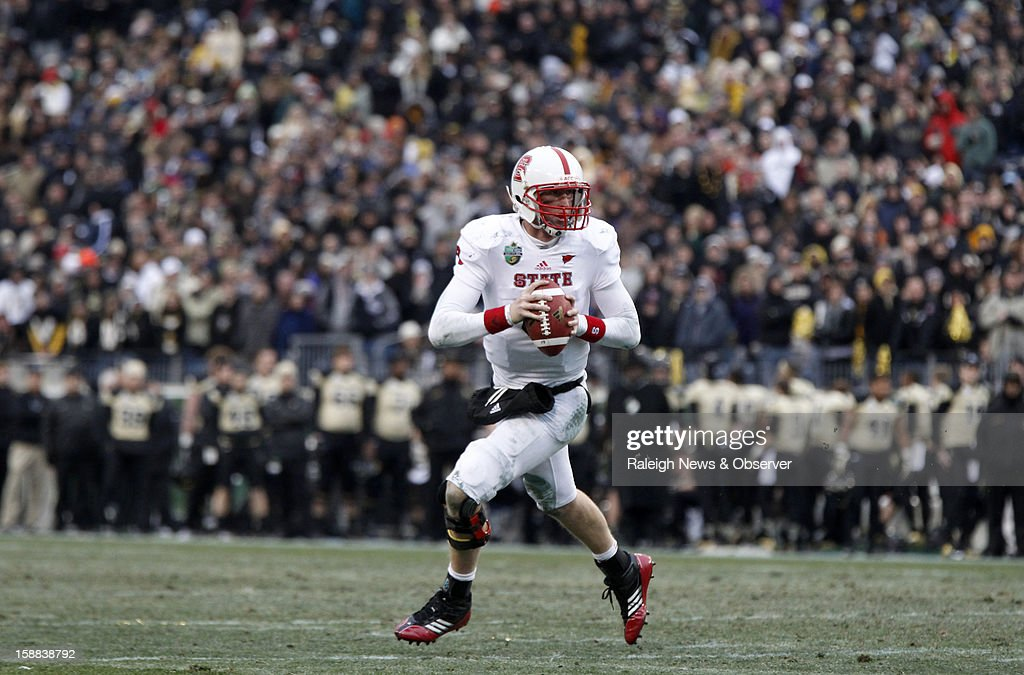 N.C. State quarterback Mike Glennon (8) looks for receivers downfield during the second half of the Franklin American Mortgage Music City Bowl at LP Field in Nashville, Tennessee, Monday, December 31, 2012. The Vanderbilt Commodores defeated the N.C. State Wolfpack, 38-24.