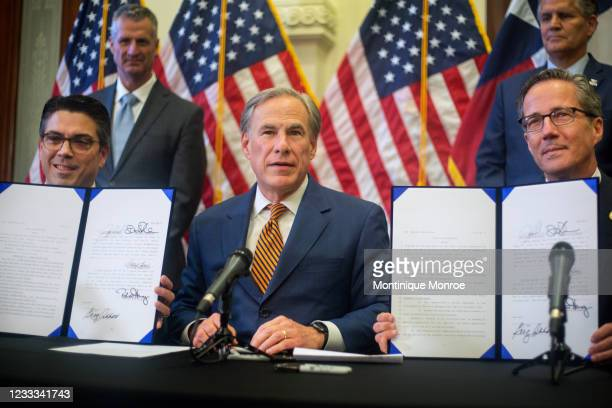 State Rep. Chris Paddie, Texas Governor Greg Abbott and State Senator Kelly Hancock show off Senate Bills 2 and 3 during a press conference at the...