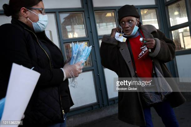State Representative Chynah Tyler, left, talks about the Covid-19 pandemic with resident Janine Edwards while handing out face masks at Nubian...