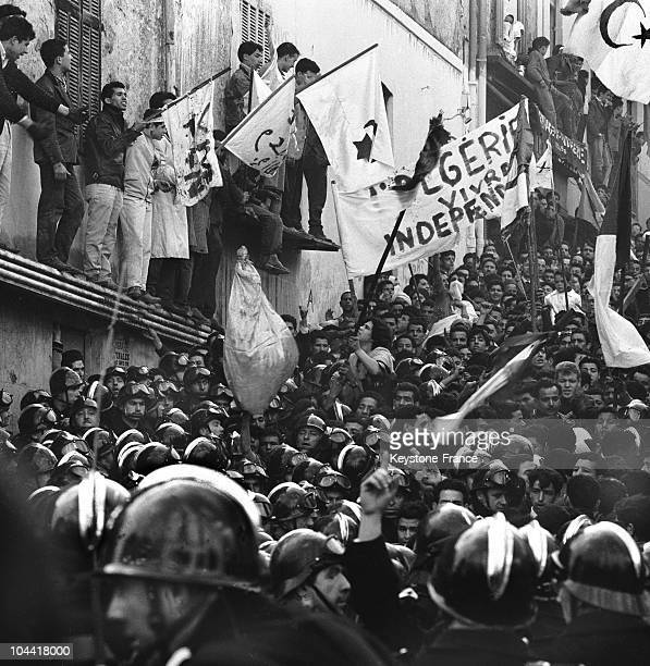 State security policemen controlling a violent Muslim demonstration in the Belcourt neighborhood of Algiers during a visit by DE GAULLE to Algeria...