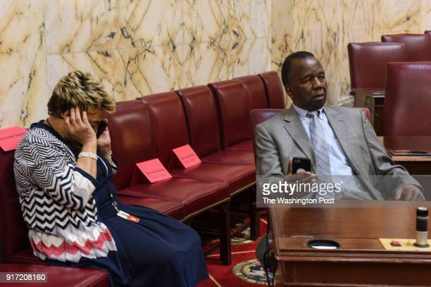 State Senator Ulysses Currie right waits for proceedings to begin as his wife Shirley GravelyCurrie left speaks on the phone in the Senate Chamber at...