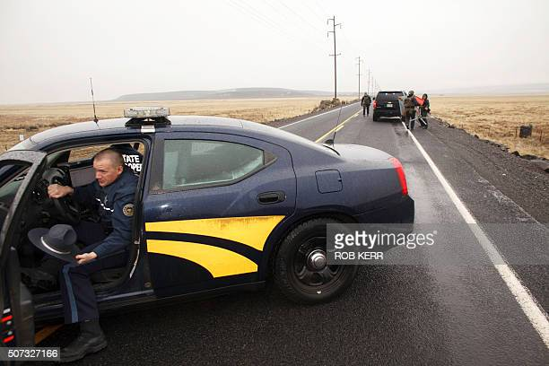A state trooper gets out of his car as they block a road 4 miles from the Malheur Wildlife Refuge Headquarters near Burns Oregon on January 28 2016...
