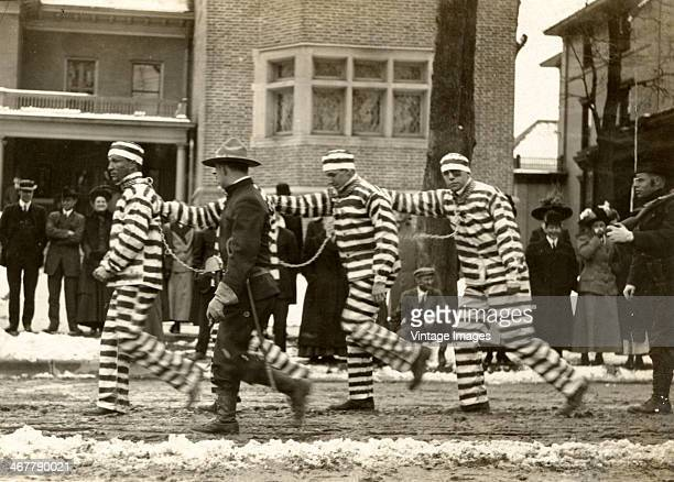 A state trooper marches a group of convicts along a snowy street USA circa 1910