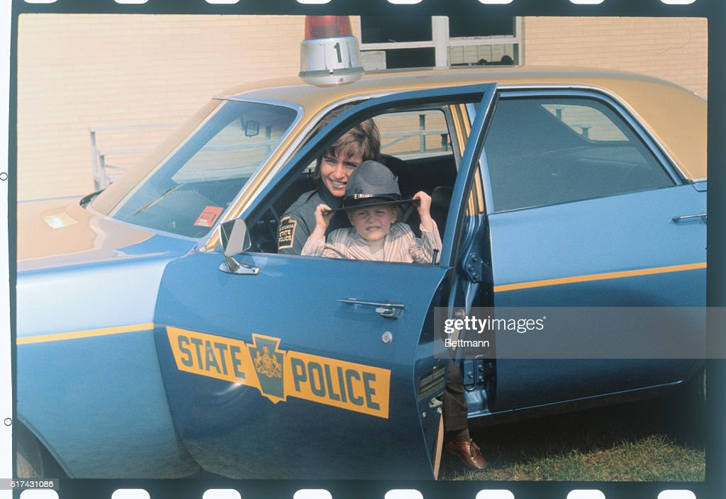 Female State Trooper with Son in Patrol Car : News Photo