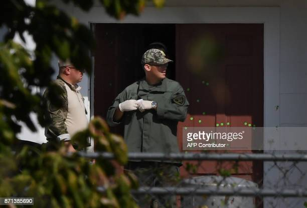 A state trooper walks past the bullet riddled main door of the First Baptist Church after a mass shooting that killed 26 people in Sutherland Springs...