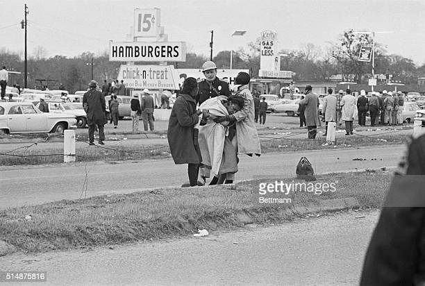 State trooper watches as Civil Rights marchers help an unconscious woman who fell as mounted police officers attacked marchers in Selma, Alabama.