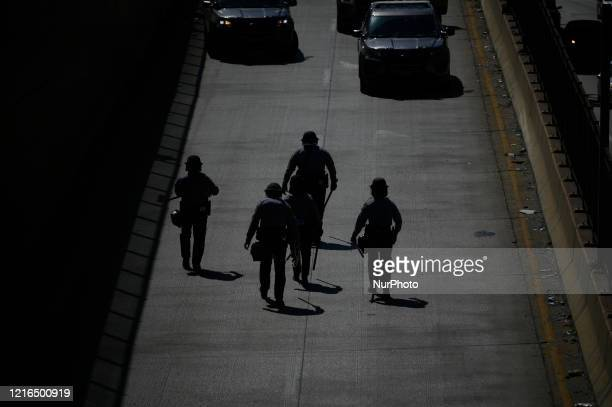 State troopers in riot gear walk up a blocked exit of the Vine Express way as protestors clash with police near City Hall in Philadelphia PA on May...