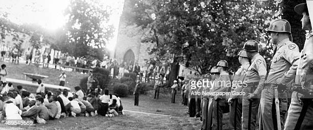State troopers lined up outside a mass rally staring down civil rights demonstrators conducting a sit in in front of a church during the Cambridge...