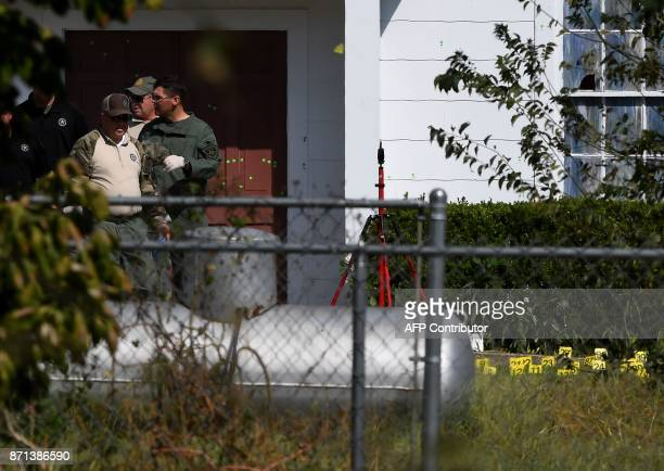 State troopers walk past the bullet riddled main door of the First Baptist Church after a mass shooting that killed 26 people in Sutherland Springs...