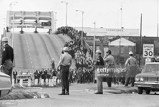 State troopers watch as marchers cross the Edmund Pettus Bridge over the Alabama River in Selma Alabama as part of a civil rights march on March 9...