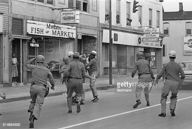 State troops wrestle a man to the ground when he is found on the streets of Rochester New York after curfew
