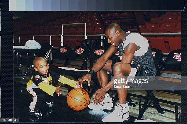 AR State Univ student Arthur Agee subject of documentary film Hoop Dreams dribbling basketball as son Anthony happily looks on in AR State Univ gym