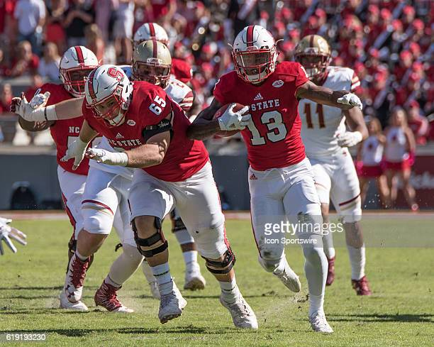 State Wolfpack wide receiver Bra'Lon Cherry breaks a run with NC State Wolfpack offensive guard Garrett Bradbury leading the block in the first half...