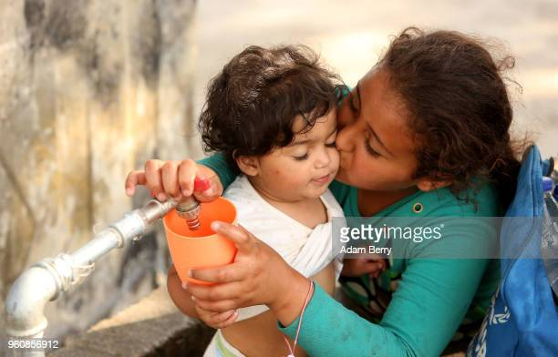 A stateless refugee girl from Iraq kisses her brother while pouring water at the Moria refugee camp on May 20 2018 in Mytilene Greece Despite being...