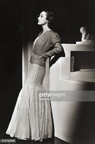 Stately Joan Crawford, MGM star, is a pictured of loveliness in a gown of red and white stripes, with tailored jacket of red linen, enhanced with...