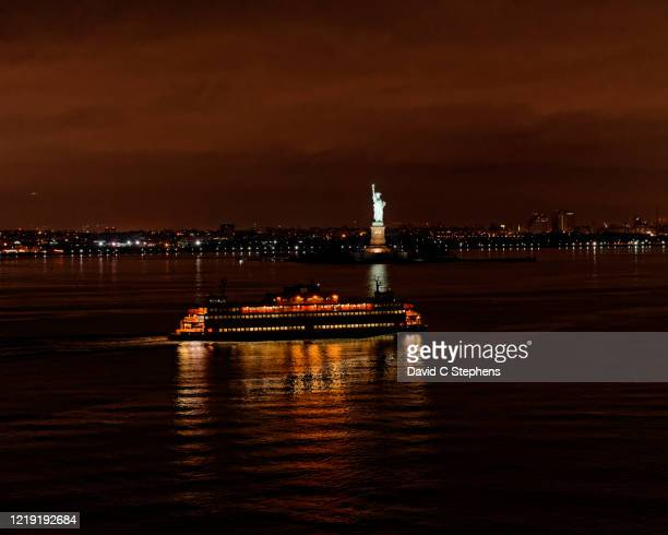 staten island ferry passes in front of statue of liberty - staten island ferry stock pictures, royalty-free photos & images