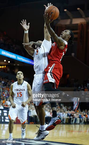 NC State's Cat Barber drives to the basket past Virginia's Justin Anderson during the first half on Wednesday Jan 7 at John Paul Jones Arena in...
