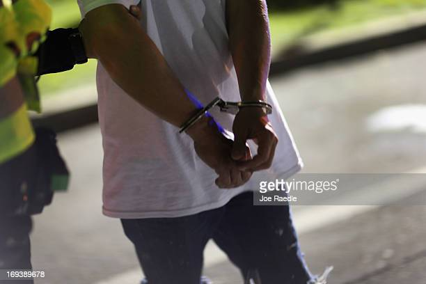 A person suspected of drunk driving is handcuffed by police during a DUI checkpoint on May 23 2013 in Miami Florida The National Transportation...