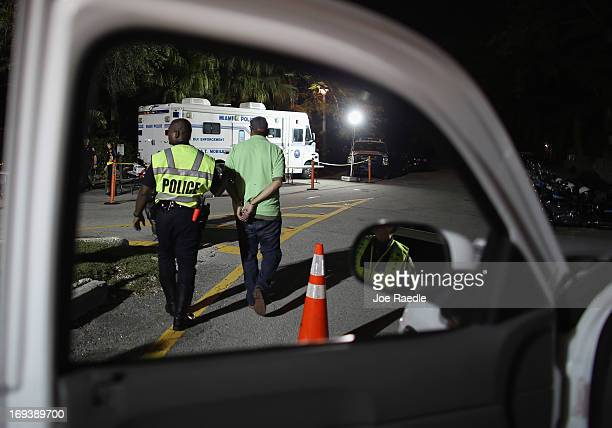 City of North Miami Beach police officer Duhamel Jeanite walks with a driver after he was handcuffed for suspicion of driving under the influence...