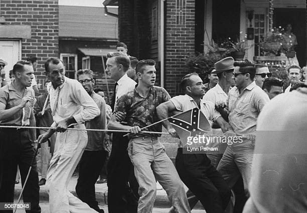 States Rights demonstrators holding Confederate flags while using rope to block entrance against school integration