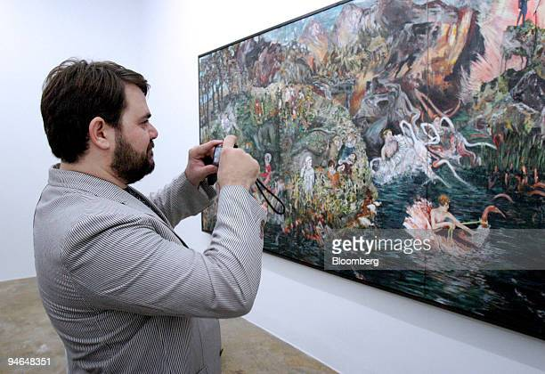 Stathis Panagoulis of The Breeder Gallery in Athens Greece takes a photo of The Great Barrier Wreath by Hernan Bas at the Rubell Family Collection...