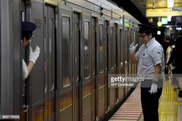 A station attendant at a platform greets a conductor in a subway in Tokyo on July 1 2017 Tokyo will hold a local election on July 2 / AFP PHOTO /...