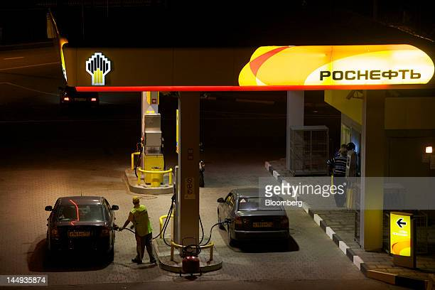 A station attendant fills a customer's vehicle with fuel at a gas station operated by OAO Rosneft Russia's biggest oil producer in Moscow Russia on...