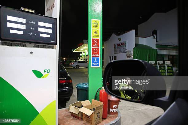 A station attendant refuels an automobile at a gas station operated by Forte Oil Plc in Abuja Nigeria on Wednesday Oct 21 2015 A drop in crude prices...