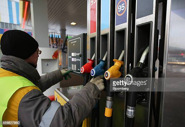 A station attendant selects a fuel nozzle from a pump before refueling a vehicle at an OAO Rosneft gas station in Moscow Russia on Tuesday Dec 2 2014...
