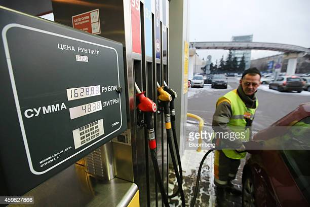 A station attendant watches the volume gauge as he refuels a vehicle at an OAO Rosneft gas station in Moscow Russia on Tuesday Dec 2 2014 Russia...