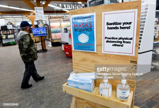 """Station inside the entrance to Weaver's Hardware with hand sanitizer and disposable face masks, a sign that reads """"PA State Mandate Face Masks..."""