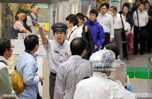 A station staff explains to commuters as the service suspended due to the Typhoon Wipha approaching at JR Shin Urayasu Station on October 16 2013 in...