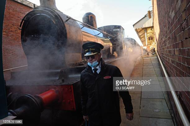 Station staff prepare a steam train before it runs along the East Lancashire Railway's line from Bury station in northern England on August 29 on one...