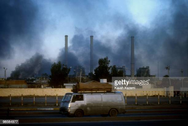 A station wagon with two coffins on its roof draped in blankets speeds past an electric power plant bombed by the Allied forces in Baghdad with huge...