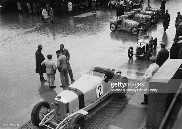 Stationary racing cars and groups of men on forecourt Photograph by Zoltan Glass c1930 Stationary racing cars and groups of men on forecourt...
