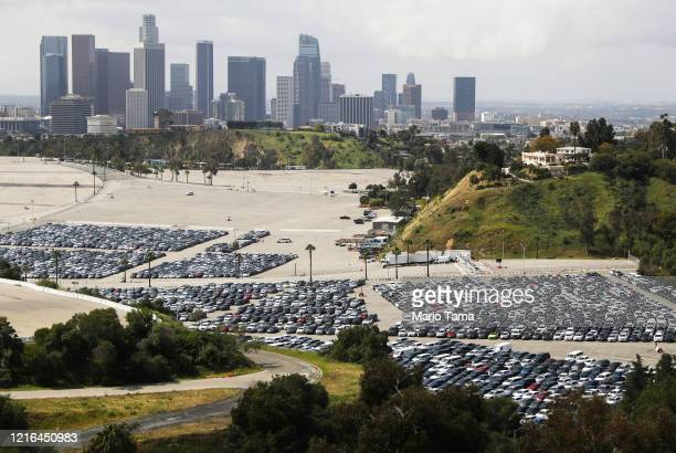 Stationed rental cars are parked in a lot at Dodger Stadium, with the downtown skyline in the background, amid the coronavirus pandemic on April 2,...