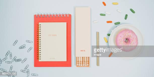 Briefpapier van boven met laptop potloden donut