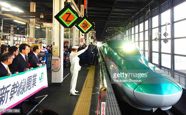 Stationmaster gives the signal for the Hakodate Hokuto bound 'Hayate 93' Shinkansen bullet train at Morioka Station on March 26 2016 in Morioka Iwate...