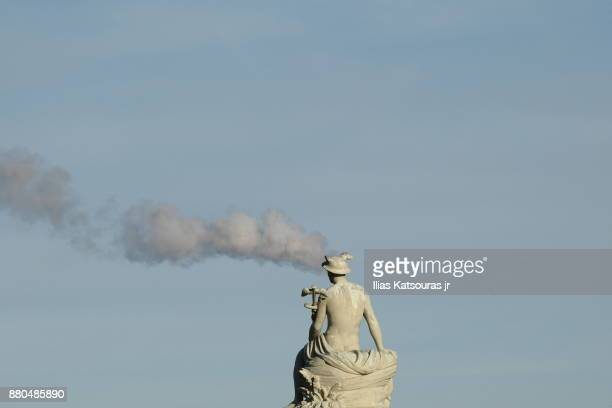 Statue against clear sky, with smoke coming out of the head