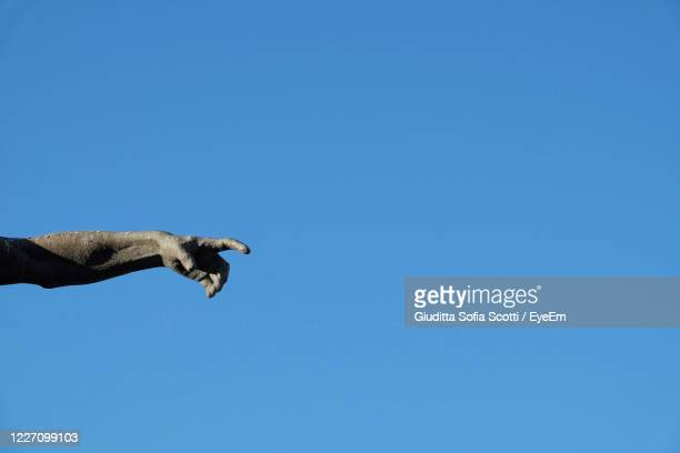 statue arm with pointing hand, blue sky as background - statue stock pictures, royalty-free photos & images