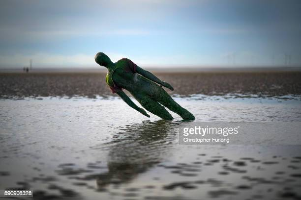 A statue at Antony Gormley's art installation 'Another Place' at Crosby Beach subsides in the sand on November 12 2017 in Liverpool England