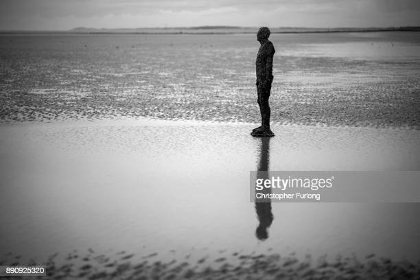 A statue at Antony Gormley's art installation 'Another Place' at Crosby Beach stands in the sand on November 12 2017 in Liverpool England